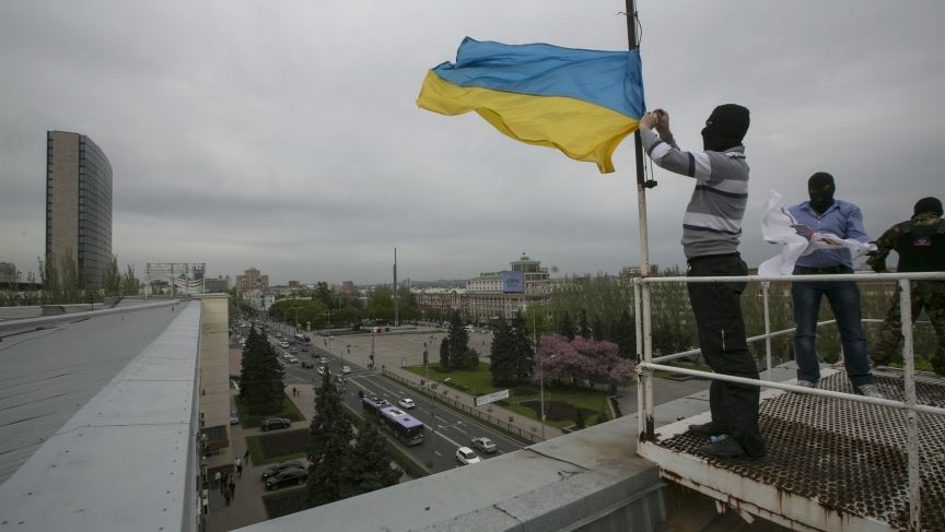 Masked pro-Russian activists haul down the Ukrainian flag from the top of another government building in eastern Ukraine, Monday.