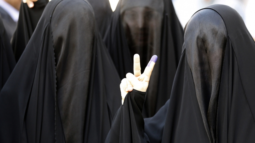 A woman in Baghdad shows her ink-stained finger after voting.