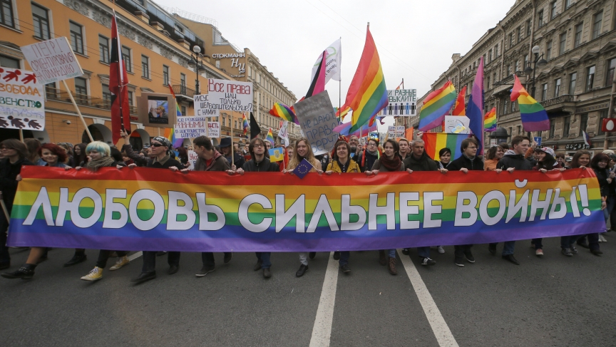 "Gay rights activists march with a banner during a May Day rally in St. Petersburg. The banner reads, ""Love is stronger than war!"""