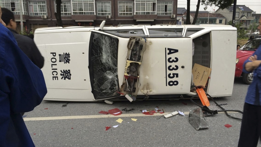 A police car is seen smashed and overturned as demonstrators protest against the construction of a waste incinerator in Hangzhou, China.