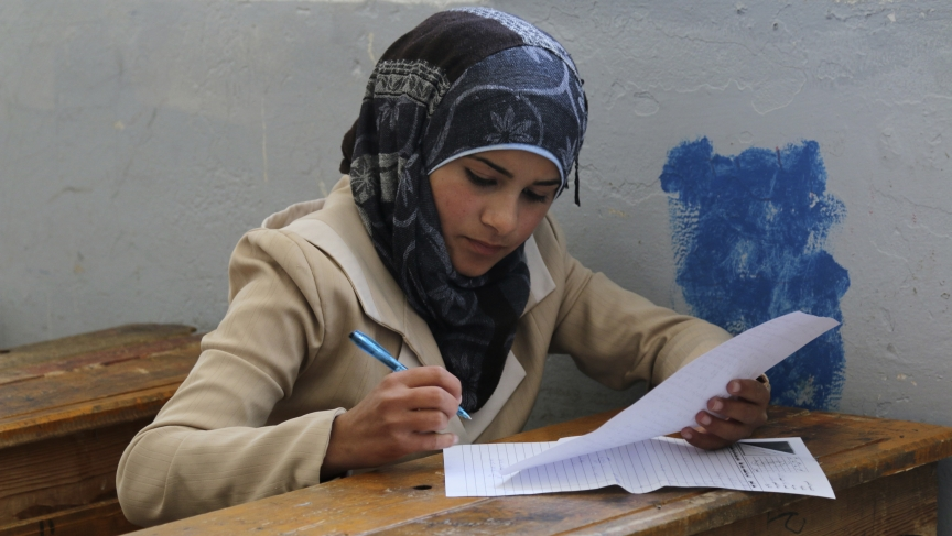 A student takes a test in Hama, Syria.  Despite the ongoing war, students in many parts of Syria are taking comprehensive exams.