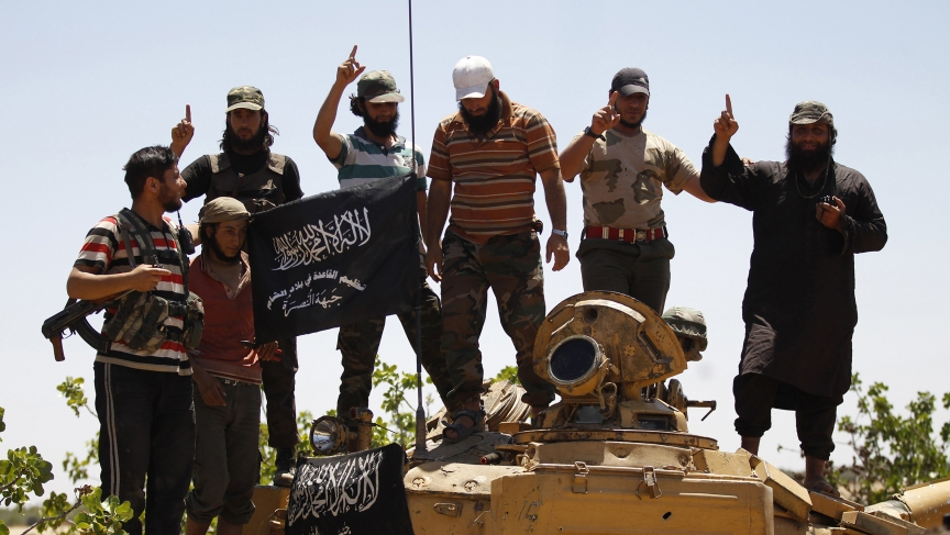 Members of the Islamist Syrian rebel group, Jabhat al-Nusra, pose on top a tank in northern Syria earlier this year.