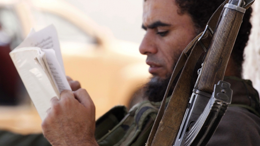 An Islamist rebel fighter reads a book while resting next to a weapon in the Hama countryside.