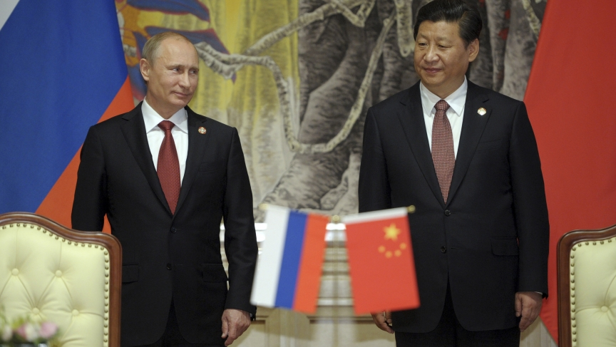 Russia's President Vladimir Putin (L) is greeted by his host, Chinese counterpart Xi Jinping in Shanghai on May 21, 2014.
