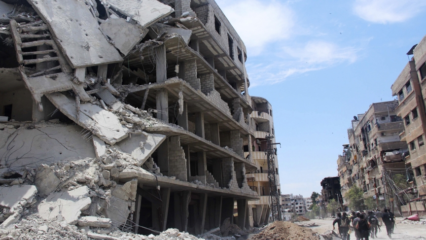 Rebel fighters carry their weapons as they run past damaged buildings to avoid snipers loyal to Syria's President Bashar al-Assad in the Mleha suburb of Damascus on May 26, 2014.