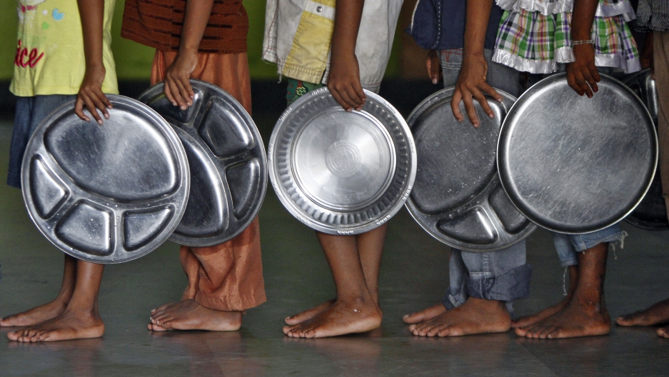 Children holding plates wait in a queue to receive food at an orphanage run by a non-governmental organisation in the southern Indian city of Chennai.