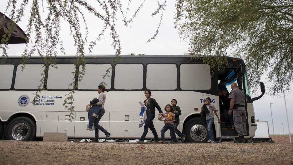 Women and children disembark from a bus marked with the insignia of the ICE