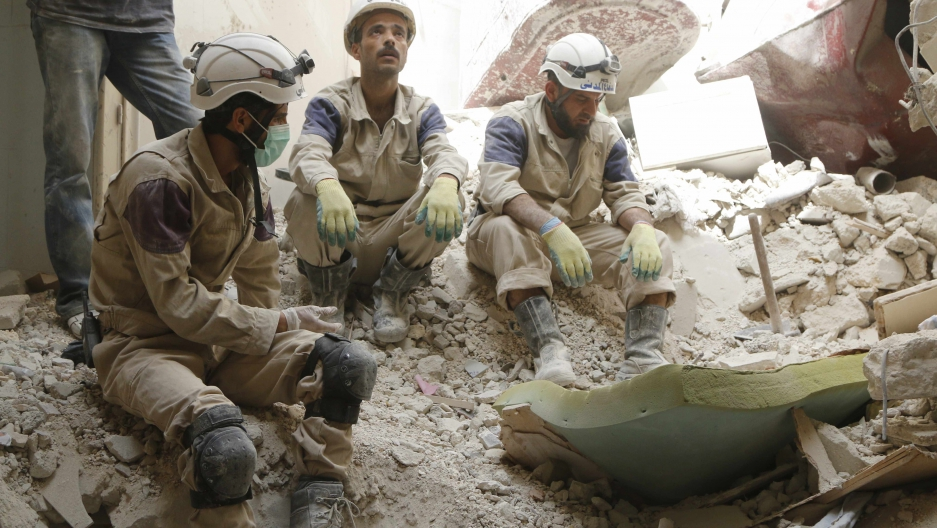 Three men sit in rubble in white helmets