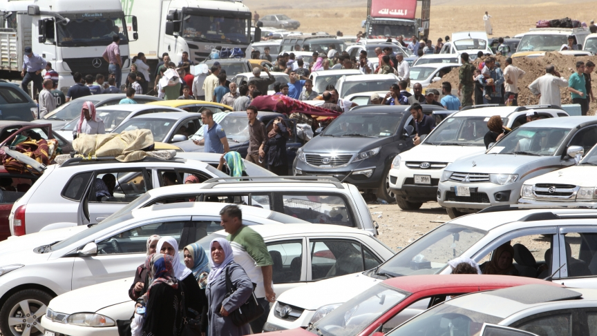 Families fleeing violence in northern wait at a checkpoint on the edge of Iraq's autonomous Kurdish region.  Half-a-million people are believed to have fled the city of Mosul in 24 hours.