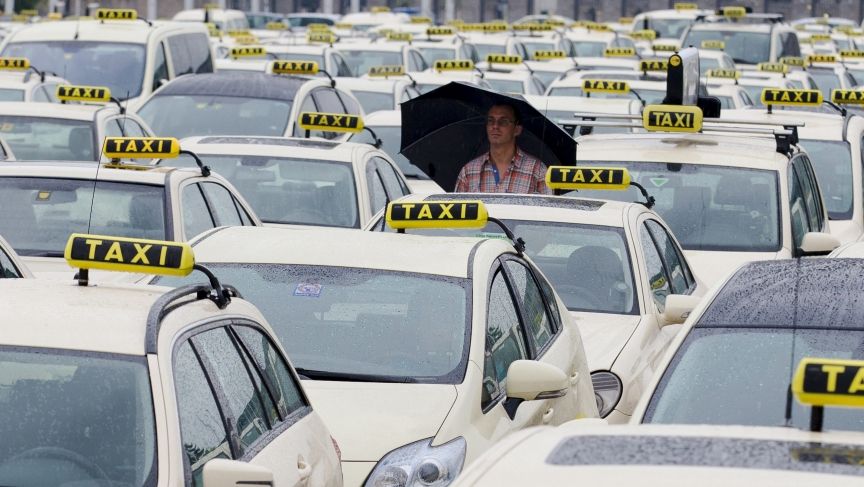A man attends an Europe-wide protest of licensed taxi drivers against taxi hailing apps. Drivers in the United States also say services like Uber and Lyft are some of the many threats to their jobs.