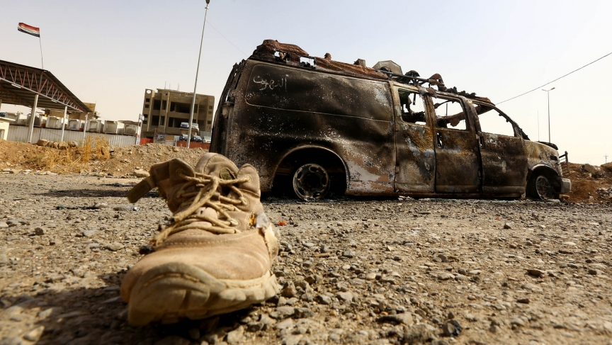 A burnt vehicle belonging to Iraqi security forces is pictured at a checkpoint in east Mosul on June 11, 2014, one day after radical Sunni Muslim insurgents seized control of the city.