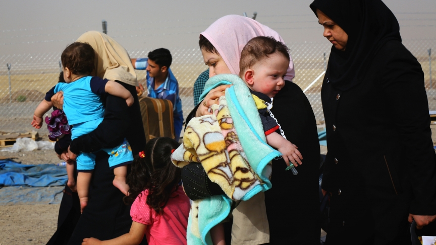 Families fleeing the violence in the Iraqi city of Mosul arrive at a checkpoint on the outskirts of Arbil.