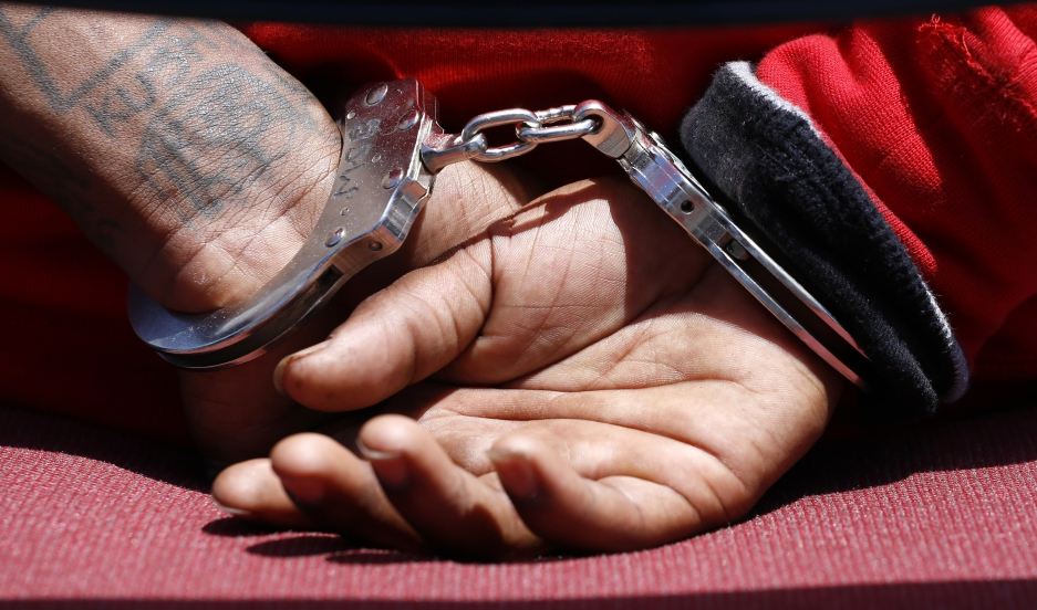 The handcuffs of a suspected member of the Broadway Gangster Crips street gang is seen while being interviewed by a law enforcement officer after he was arrested in Los Angeles on June 17, 2014.