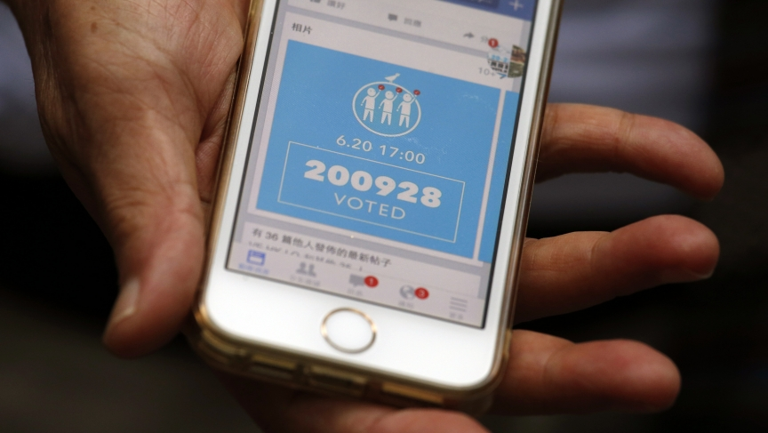 A Hong Kong resident shows a Facebook page announcing the number of votes in the city's unofficial pro-democracy referendum. Many Hong Kongers believe Beijing is trying to undermine the vote with internet attacks.