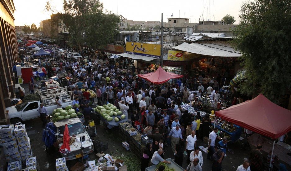 Residents of Erbil buy groceries in a local market.