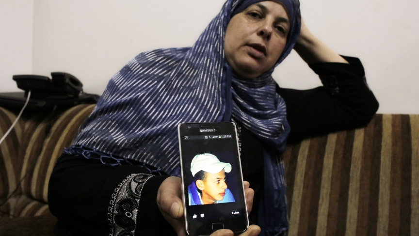 Suha, mother of 16 year-old Mohammed Abu Khudair, shows a picture of her son on her mobile phone at their home in Shuafat, an Arab suburb of Jerusalem. News of the discovery of Mohammed's body sparked clashes on Wednesday between rock-throwing Palestinian