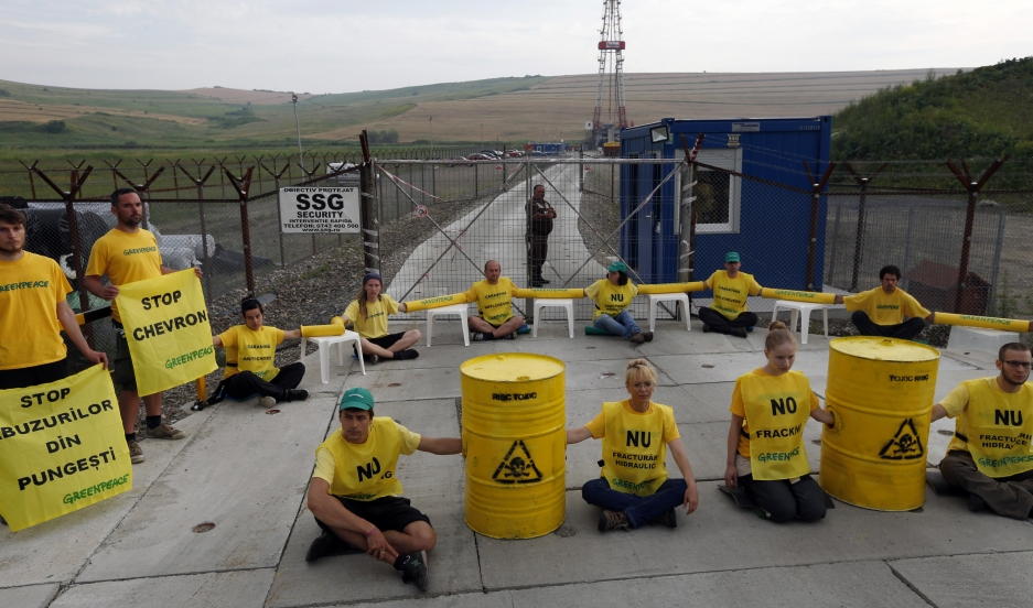 Greenpeace activists sit chained in front of Chevron's drilling site for shale gas during a protest in the village of Pungesti, Romania.