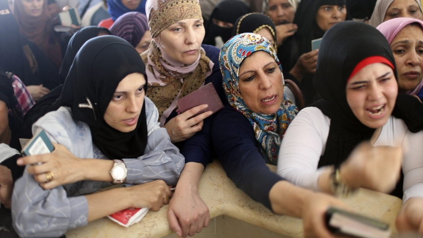 Women hoping to cross into Egypt present their passports as they wait at the Rafah crossing between Egypt and the southern Gaza Strip on July 12, 2014. Egypt's state news agency said Egyptian authorities had decided to open the Rafah border crossing to Ga
