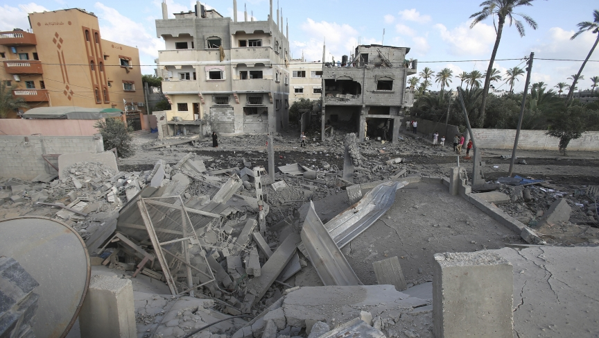 Palestinians look at the rubble of a house which police said was destroyed in an Israeli air strike in Deir El-Balah in the central Gaza Strip July 14, 2014.
