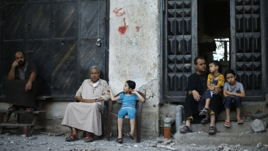 Palestinians sit outside their house that is located opposite to the house of top Hamas political leader Mahmoud Zahar which police said was targeted in an Israeli air strike in Gaza City