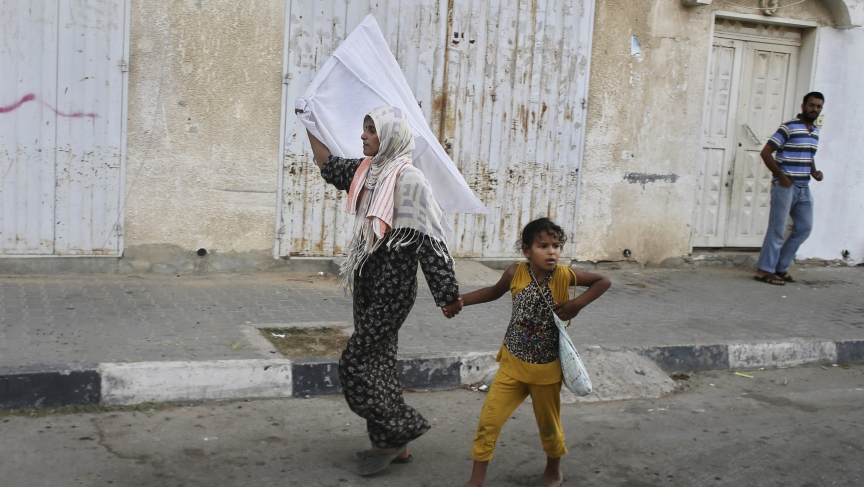 A Palestinian woman waves a white flag of surrender after an Israeli shelling in Gaza.