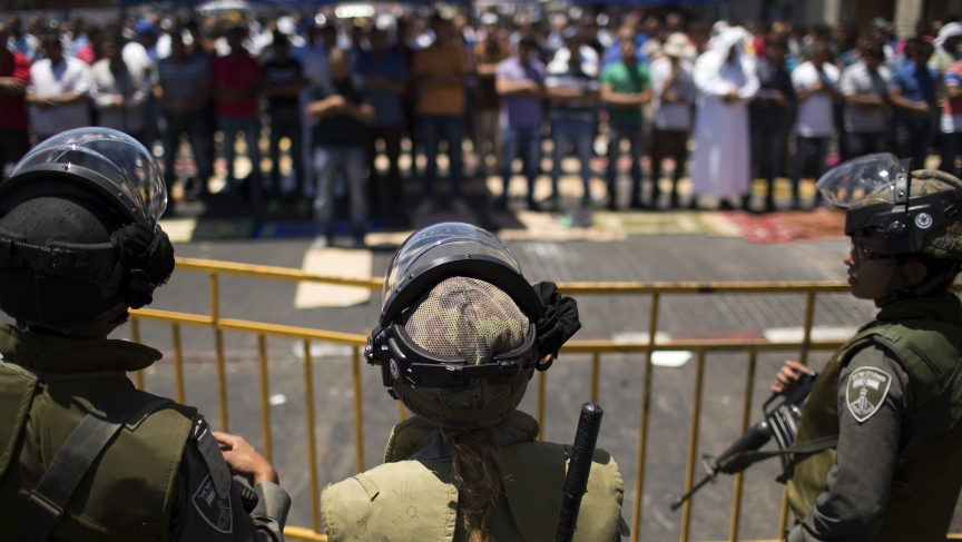 Israeli police stand guard behind as Palestinians pray on the last Friday of the holy month of Ramadan outside of the Old City in Jerusalem, on July 25, 2014.