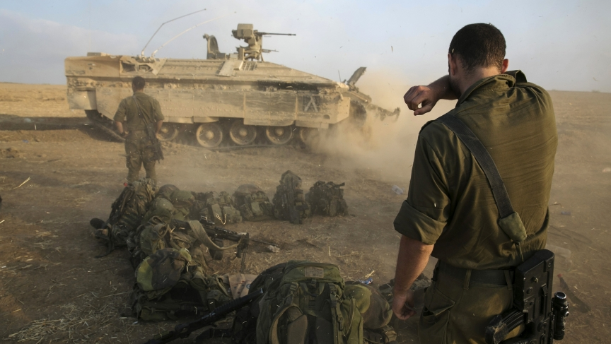 An Israeli soldier stands at a staging area after crossing back into Israel from Gaza on July 28, 2014.