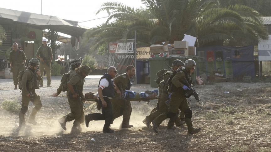 Israeli soldiers evacuate a comrade after he was wounded in a Palestinian mortar strike inside Israel on Monday.