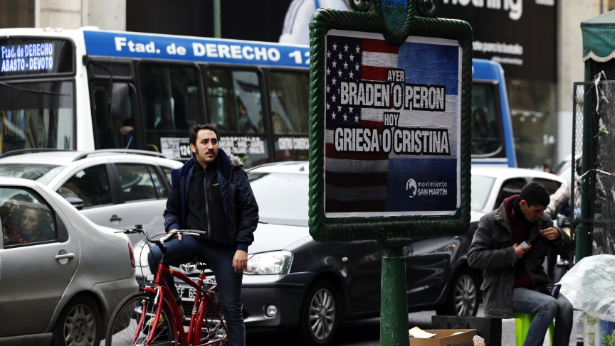 "A man looks at a poster placed on an advertising board that reads ""Yesterday, Braden or Peron - Today: Griesa or Cristina"", in Buenos Aires on July 29, 2014. Argentine debt negotiators held talks in New York on Tuesday with the U.S. mediator in the South"