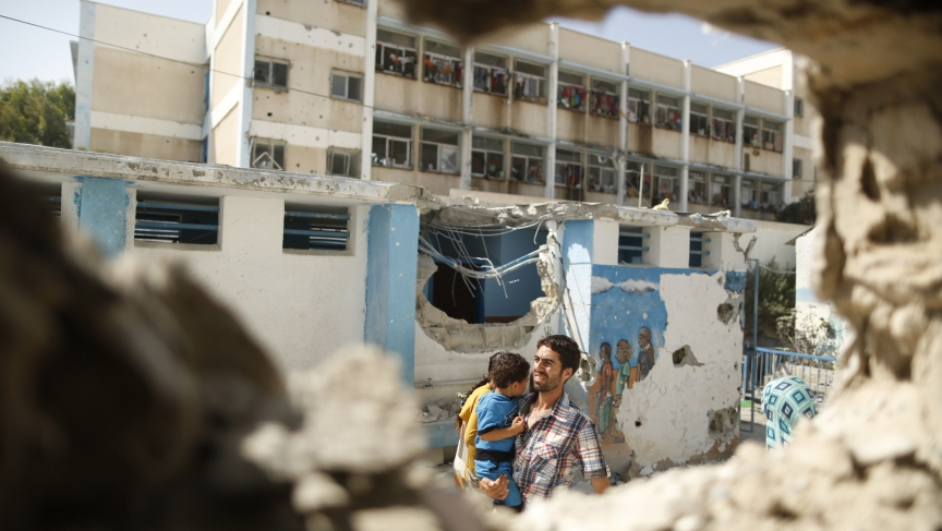 A Palestinian man, pictured through a damaged classroom, carries a boy as he walks at a United Nations-run school in the Jebaliya refugee camp in the northern Gaza Strip on July 30, 2014. Witnesses say the school, which is sheltering Palestinians displace