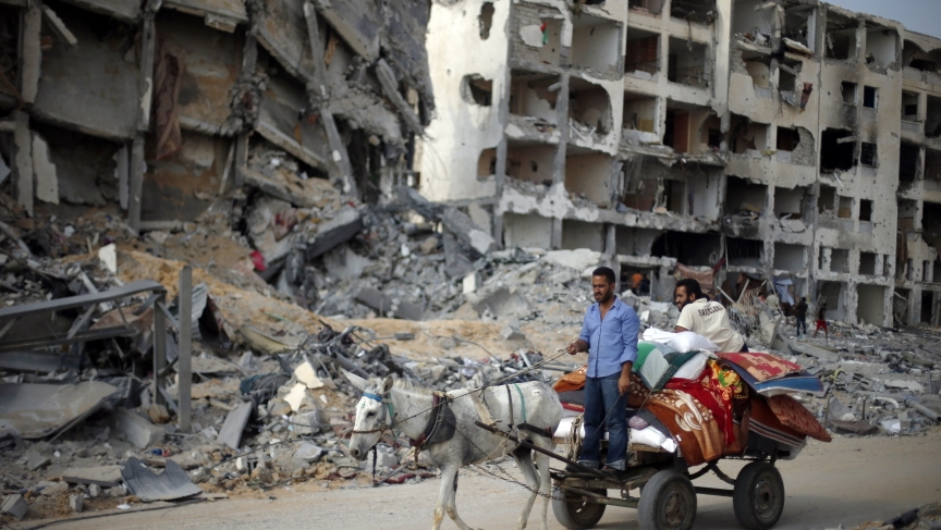 Palestinians ride a donkey cart past destroyed and badly damaged residential buildings as they return to Beit Lahiya town, which witnesses said was heavily hit by Israeli shelling and air strikes during the Israeli offensive.