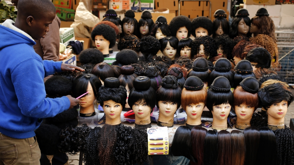 A man prepares wigs as he waits for customers in downtown Johannesburg.
