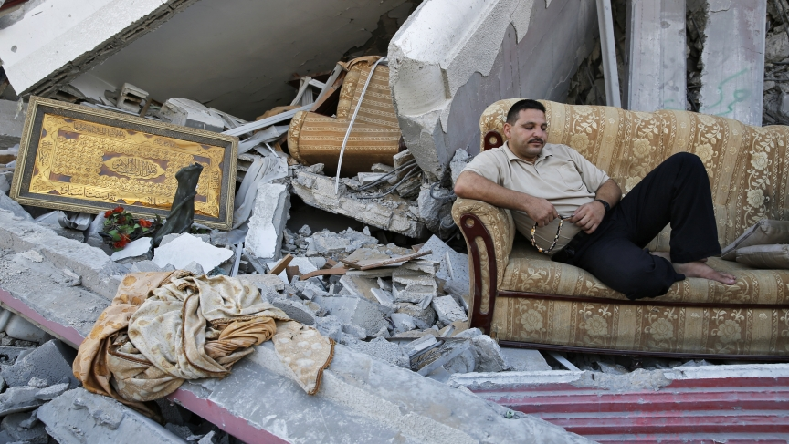 A man sits amid the ruins of destroyed homes in the Gaza Strip. Reconstruction cannot really start till Israel opens the frontier for cement and other building materials.