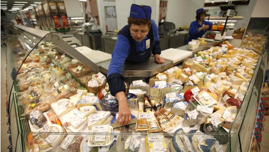 A worker arranges cheese for sale at a grocery store in Moscow on August 7, 2014. Moscow imposed a total ban on imports of many Western foods on Thursday in retaliation against sanctions over Ukraine.