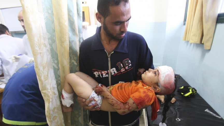 A man carries a Palestinian girl, whom medics said was wounded in an Israeli air strike, at a hospital in Khan Younis in the southern Gaza Strip, Friday.