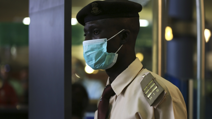 An immigration officer wears a face mask at the Nnamdi Azikiwe International Airport in Abuja August 11, 2014.