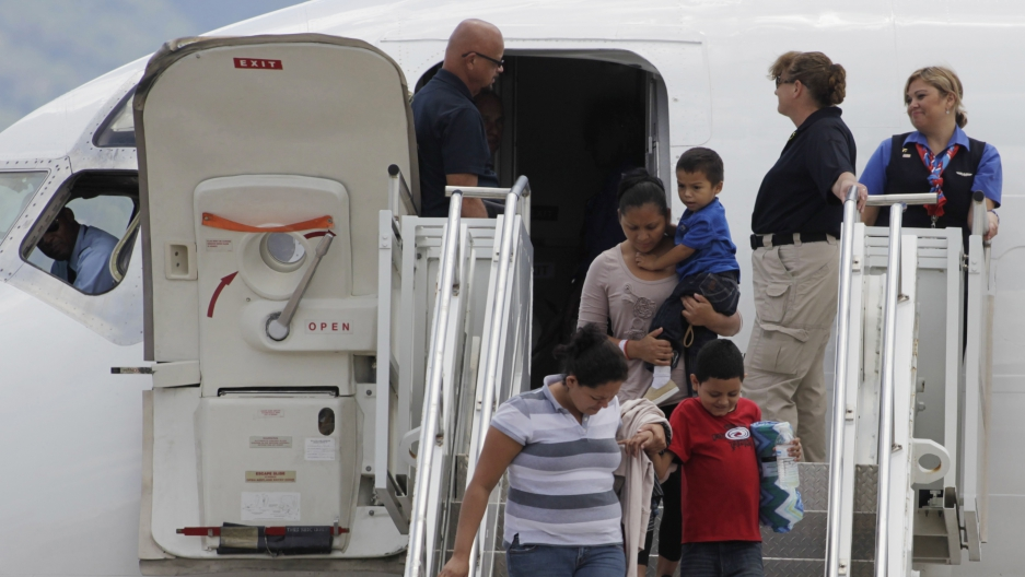 Women and children disembark from a plane, with agents around them