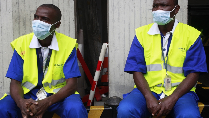 Workers wearing protective masks sit at the Felix Houphouet Boigny international airport in Abidjan. Ivory Coast on Monday banned air travelers from Liberia, Guinea and Sierra Leone, the three countries worst-hit by the Ebola outbreak.