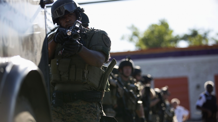 A police officer holds his riot gun while demonstrators protest the shooting death of teenager Michael Brown in Ferguson, Missouri, on August 13, 2014.