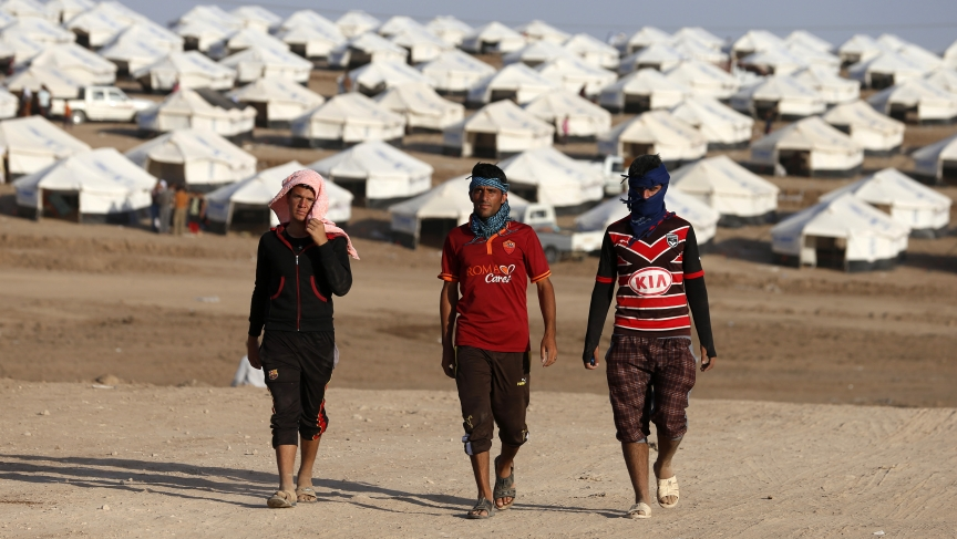 Displaced people from the minority Yazidi sect, who fled the violence in the Iraqi town of Sinjar, walk in the Bajed Kadal refugee camp southwest of Dohuk province on August 15, 2014.