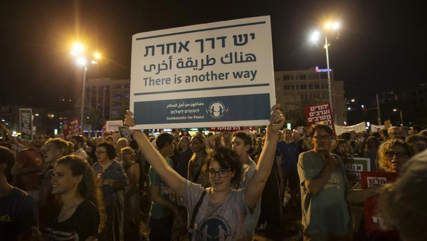 A woman holds up a placard during a peace rally in Tel Aviv's Rabin Square.