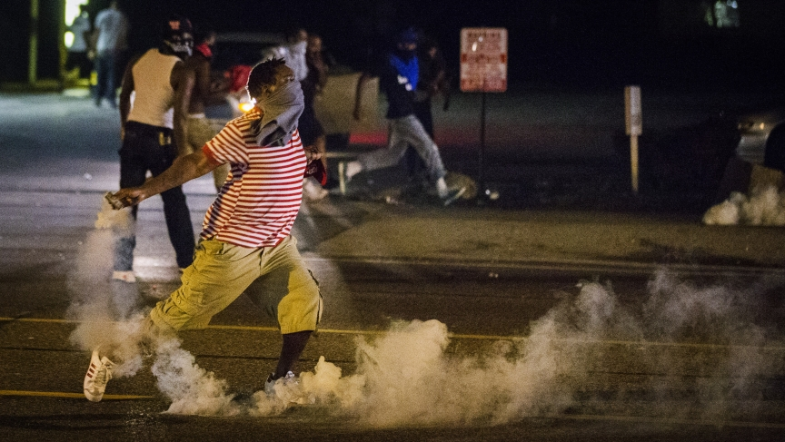 A protester picks up a gas canister to throw back towards the police after tear gas was fired at demonstrators during a protest in Ferguson, Missouri.