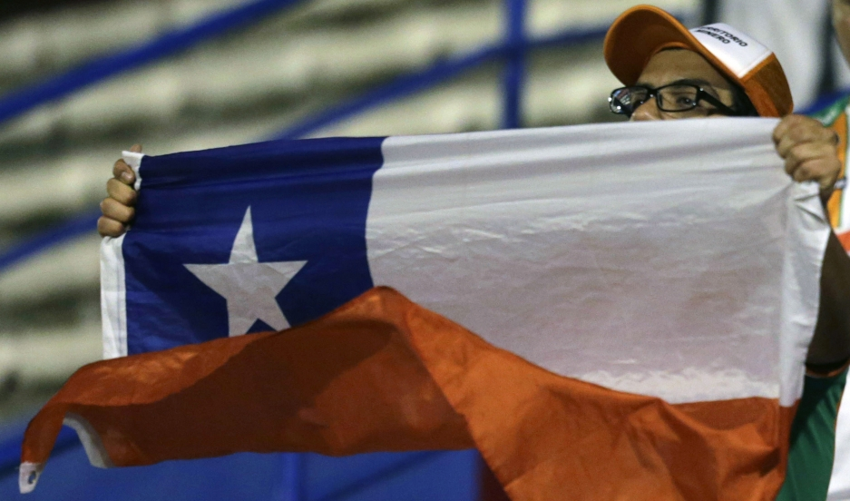 A fan of Chile's Cobresal holds a Chilean national flag before his team plays against Paraguay's General Diaz in their Copa Sudamericana soccer match in Luque near Asuncion, August 20, 2014.