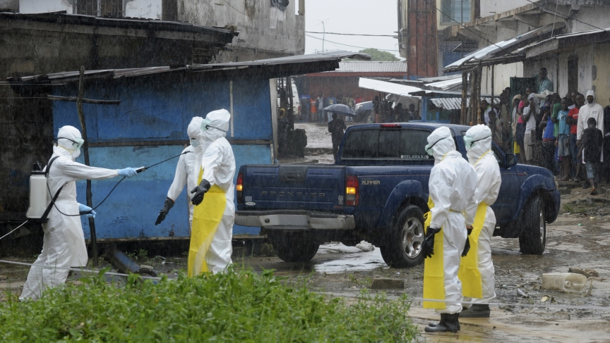 Health workers wearing protective clothing disinfect themselves after an abandoned dead body presenting with Ebola symptoms was found at Duwala market in Monrovia, Liberia, on August 17, 2014.