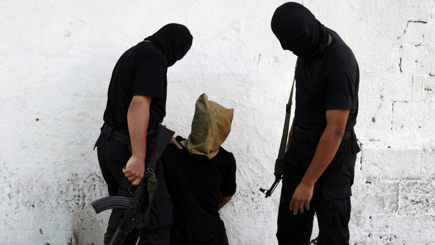 Hamas militants grab a Palestinian suspected of collaborating with Israel before being executed in Gaza City on August 22, 2014. Hamas militants killed seven Palestinians suspected of collaborating with Israel in a public execution in a central Gaza squar