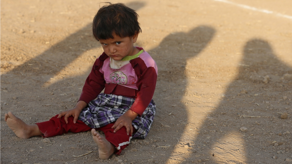 A child from the minority Yazidi sect, who fled violence in the Iraqi town of Sinjar, sits on the ground at Bajed Kadal refugee camp, southwest of Dohuk province August 23, 2014.