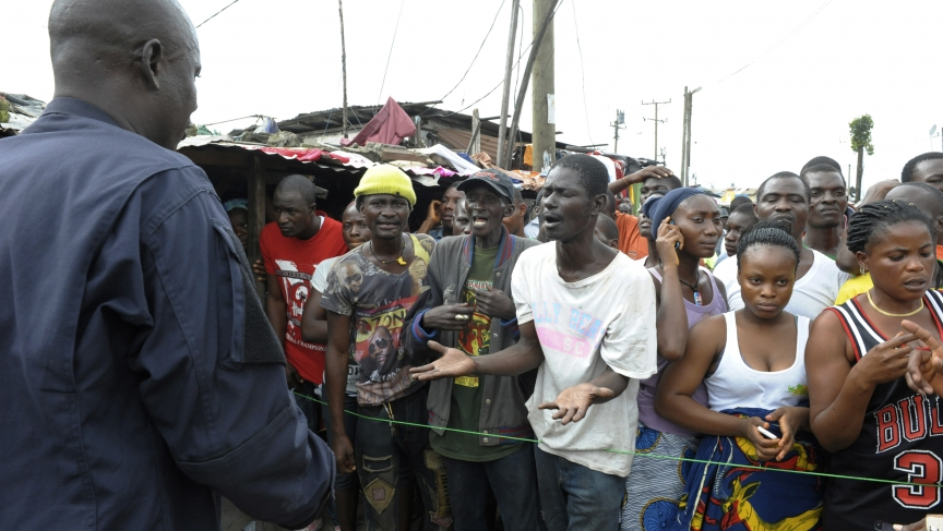 Residents in an Ebola quarantine area in the West Point of Monrovia, Liberia, complain to a security officer as they wait for their relatives to bring them food and essentials on August 23, 2014.