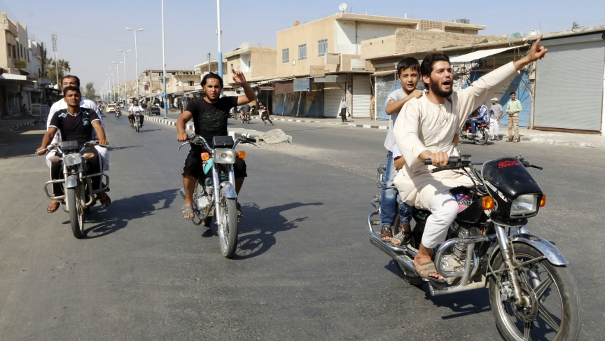 People in the Syrian city of Tabqa toured the streets in celebration after Islamic State militants took over a government air base nearby on August 24, 2014.