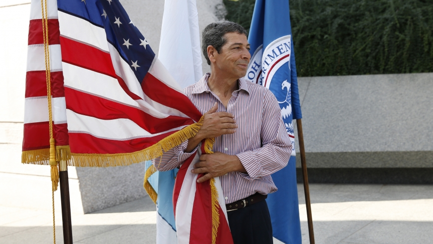 Brahim Djahra, from Algeria, clings to the Americans flag during a special naturalization ceremony held at the Martin Luther King Jr. Memorial in Washington on August 28, 2014.