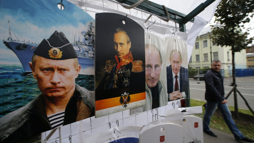A man walks past cutting boards that have been painted with images of Russia's President Vladimir Putin at a street store in the center of St. Petersburg on August 31, 2014.